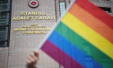 Manifestante segura bandeira do arco-íris em frente à corte de Istambul, em apoio a 11 ativistas que foram processados por terem realizado a Parada do Orgulho LGBT no ano passado, enfrentando proibição imposta pelas autoridades. As acusações foram derrubadas. Foto: OZAN KOSE / AFP