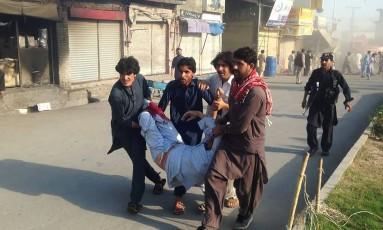 Ferido é carregado após ataque contra mercado em Parachinar Foto: STR / AFP