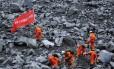 Trabalhadores procuram por sobreviventes no local do deslizamento no vilarejo de Xinmo, na China