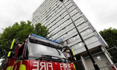 Um caminhão do bombeiro estaciona em frente a um edifício no norte de Londres. Cerca de 650 apartamentos foram esvaziados para testes de segurança após o incêndio na Grenfell Tower Foto: TOLGA AKMEN / AFP