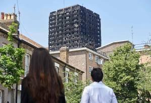 Moradores de Londres observam ruínas da Grenfell Tower após incêndio que destruiu o edifício Foto: NIKLAS HALLE'N / AFP