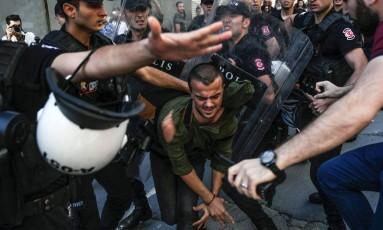 Policiais batem em um membro do grupo que defende direitos LGBTI na Turquia Foto: BULENT KILIC / AFP