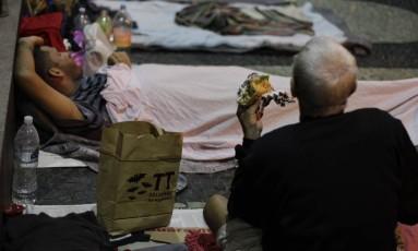 Morador de rua come hambúrguer doado por voluntários no Centro Foto: Pedro Teixeira / Agência O Globo