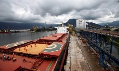 Funcionários trabalham no abastecimento de um navio com soja no porto de Santos Foto: PAULO WHITAKER / Agência O Globo