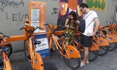 Os paulistas Daiane Martis e Vinícius Alejandro tentam alugar bicicletas em Copacabana: cada um pagou R$ 10 para pedalar, mas não conseguiu porque a estação era uma das 37 que estavam fora de operação Foto: Antonio Scorza / Agência O Globo