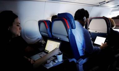 Passageiros usam notebooks em um voo saindo do aeroporto internacional John F. Kennedy (JFK), em Nova York Foto: Lucas Jackson / REUTERS