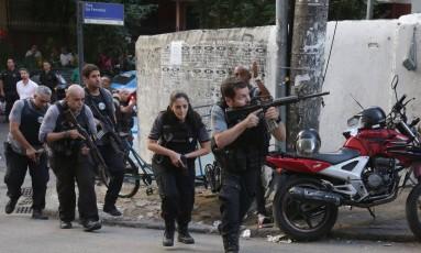 Policiais correm pela Rua Sá Ferreira, em Copacabana Foto: Márcio Alves / Agência O Globo