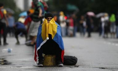 Um manifestante veste a bandeira da Venezuela em Caracas Foto: Ariana Cubillos / AP