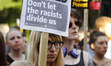 """""""Não deixem os racistas nos dividirem"""" diz cartaz de jovem em uma vígilia em frente à mesquita de Finsbury Park, que sofreu um atentado no dia 19 de junho Foto: TOLGA AKMEN / AFP"""
