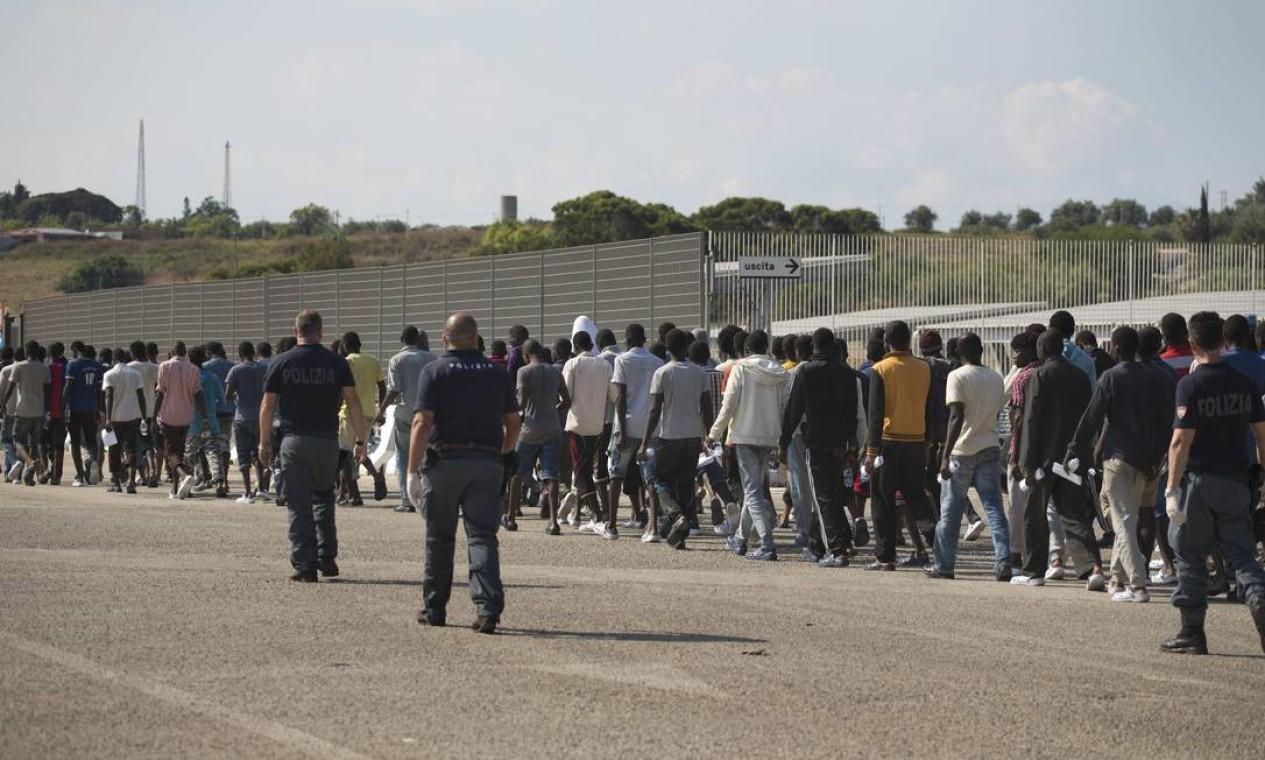 Policiais escoltam africanos no caminho para o centro de realocação no Sul da Itália . Cerca de 12 mil migrantes foram resgatados nas últimas 48 horas na costa da Líbia Foto: Emilio Morenatti / AP