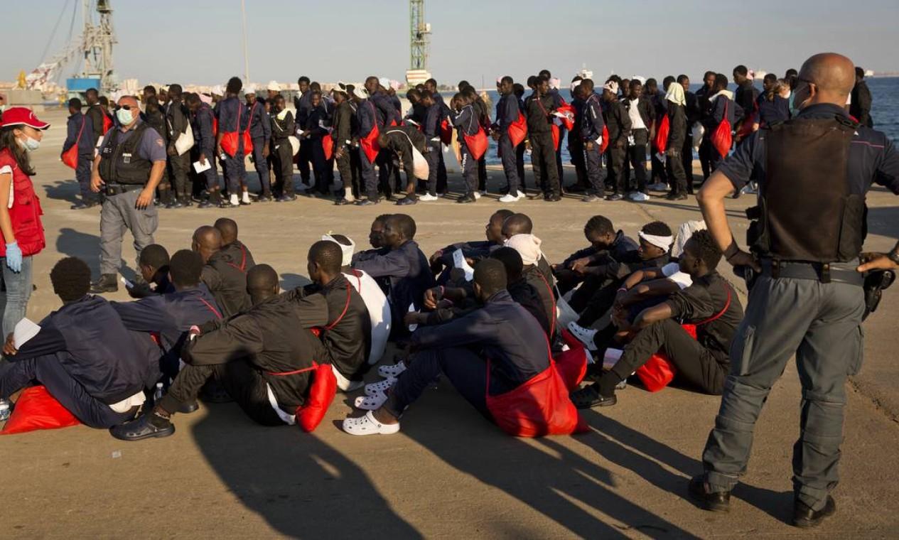 Africanos sentam no chão perto de policiais italianos, depois de chegarem no navio de resgate Golfo Azzurro no porto de Augusta, na Sicília. Na quarta-feira, a Itália ameaçou fechar seus portos a barcos de grupos humanitários que tem realizado o resgate de milhares de migrantes diariamente Foto: Emilio Morenatti / AP
