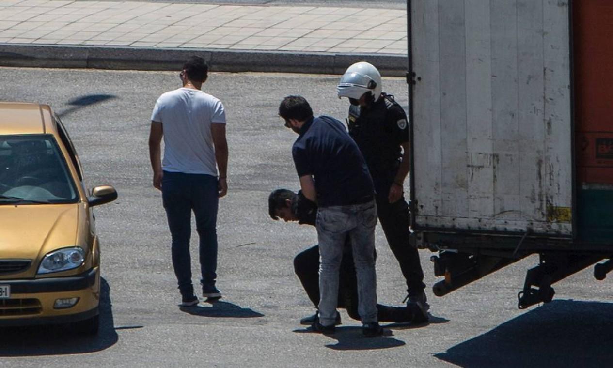 Policiais gregos prendem um imigrante em Patras, no Sudoeste da Grécia. O homem tentou se esconder em um caminhão que embarcaria em um navio para a Itália Foto: ANGELOS TZORTZINIS / AFP