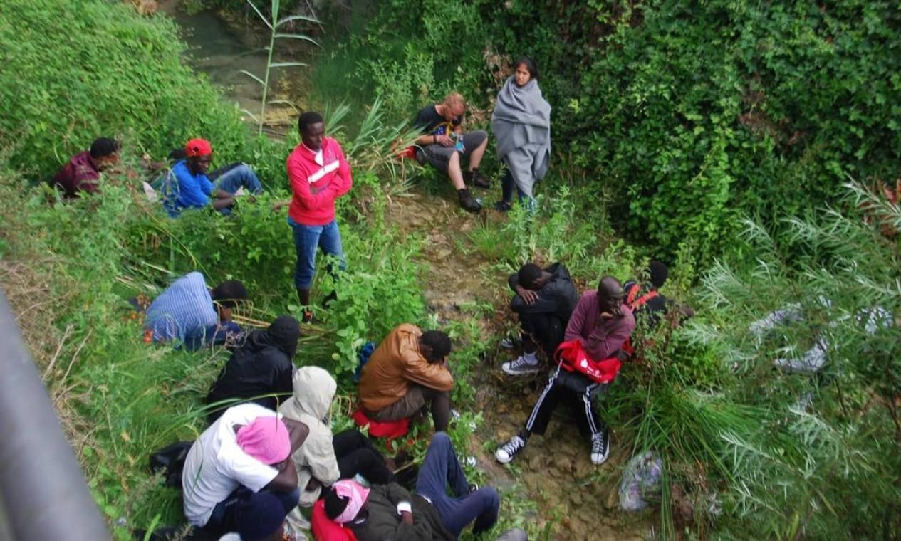Imigrantes descansam na beira do rio Roja, na cidade do Norte da Itália de Ventimiglia, enquanto tentam chegar na fronteira da França. Somente na segunda-feira, 5 mil chegaram na Itália, segundo dados oficiais Foto: Chiara Carenini / AP