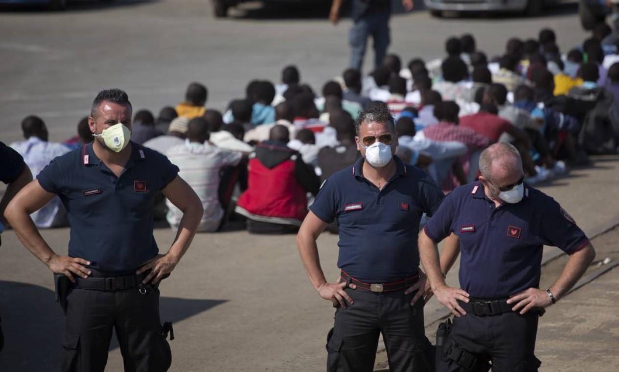 Policiais italianos observam o movimento no porto de Augusta, na Sicília. A Itália se queixa há vários anos sobre a política passiva da União Europeia (UE) diante da grave crise migratória causada pelos conflitos no Oriente Médio e na África Foto: Emilio Morenatti / AP