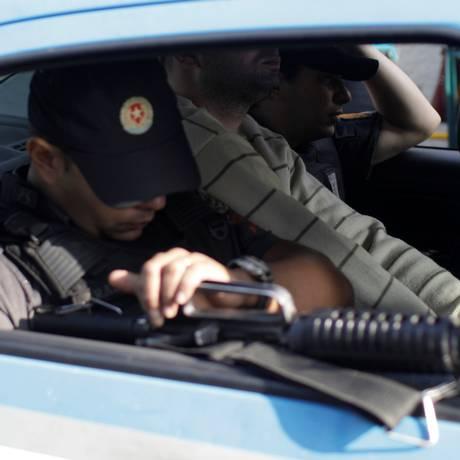 Policiais militares conduzem à prisão um colega (ao centro) acusado de participar de esquema de propinas organizado por traficantes de São Gonçalo Foto: Ricardo Moraes / Reuters