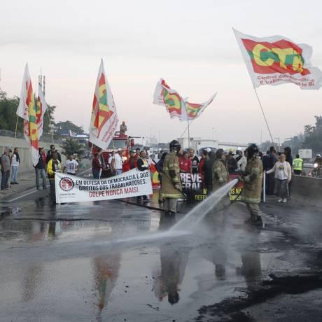 Bombeiros apagam incêndio em barricada criada por manifestantes na Avenida Brasil, na altura da Penha Foto: Pedro Teixeira / Agência O Globo