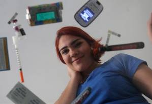"""Beatriz Scher, de 23 anos, com tudo o que usa para controlar o diabetes, inclusive seringa e bomba de insulina. Ela tem um blog sobre o tema, o """"Biabética"""" Foto: Custodio Coimbra"""