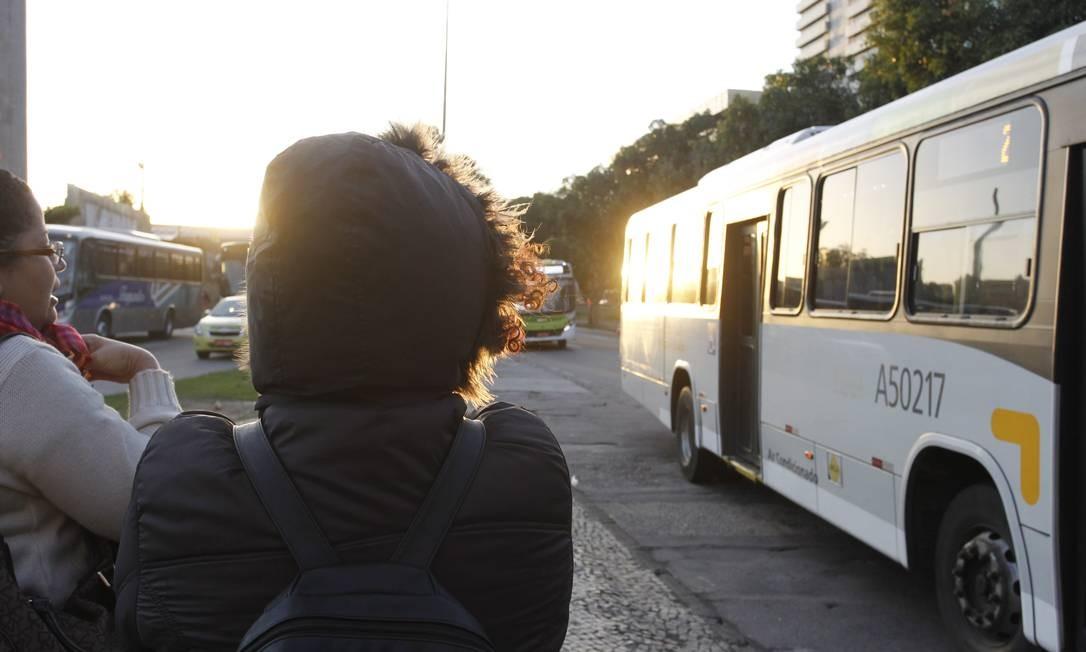 Não há previsão de chuva para esta terça-feira. Na foto, pedestres agasalhados à espera de ônibus na Cidade Nova Foto: Pedro Teixeira / Agência O Globo