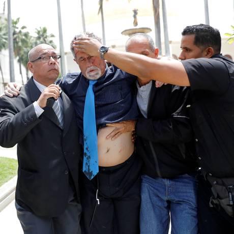 O deputado Americo De Grazia (centro) é ajudado por outros colegas após ser ferido Foto: ANDRES MARTINEZ CASARES/REUTERS