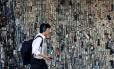 Homem passa por parede de celulares em Tóquio