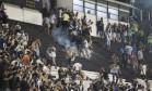 Torcedores do Vasco correm de bombas atiradas na arquibancada: momnentos de tensão após o clássico Foto: Guito Moreto / Agência O Globo