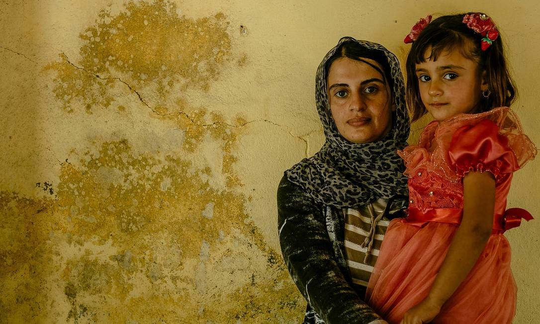 Turkia Hussein, de 25anos, e a filha, Riwazi. Elas se reencontraram após Turkia fingir estar doente e conseguir ser negociada de volta para sua família Marcio Pimenta / Agência O Globo