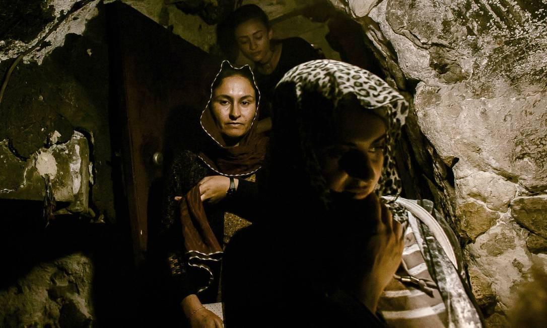 Ghazal Naser Khalaf (centro) e Turkia Hussein (direita) descem por uma estreita fenda que as leva até a fonte sagrada conhecida pelo nome de Zamzam. Todo yazidi deve fazer a peregrinação a Lalish pelo menos uma vez na vida Marcio Pimenta / Agência O Globo