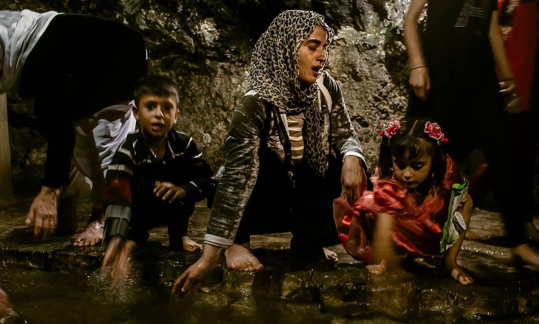"""Turkia Hussein (ao centro) com os filhos na fonte sagrada Zamzam, em Lalish, agradece por se tornar yazidi novamente: """"A comunidade está ajudando muito. Ela respeita a nossa situação"""" Foto: Marcio Pimenta / Marcio Pimenta"""