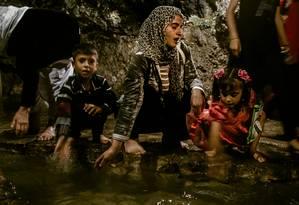 Turkia Hussein (ao centro) com os filhos na fonte sagrada Zamzam, em Lalish, agradece por se tornar yazidi novamente: