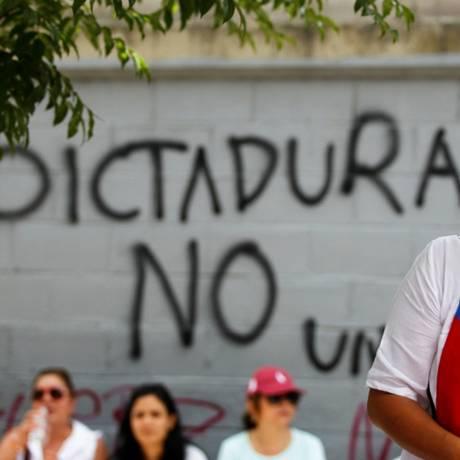 Manifstante da oposição usa bandeira da Venezuela no rosto; atrás, no muro, lê-se