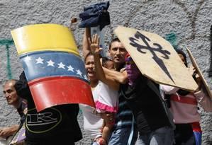 Manifestantes contra Maduro protegem família que tenta atravessar rua no meio de confrontos com policiais em Caracas Foto: Ariana Cubillos / AP