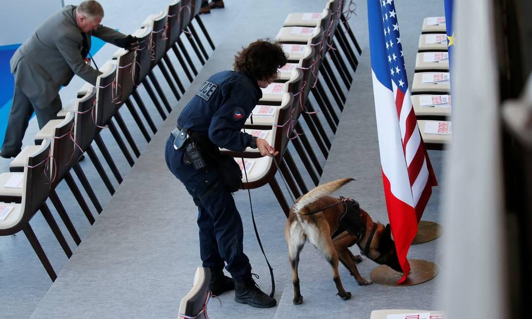 Oficiais franceses usam cão farejador durante revista de segurança na tribuna presidencial. GONZALO FUENTES / REUTERS