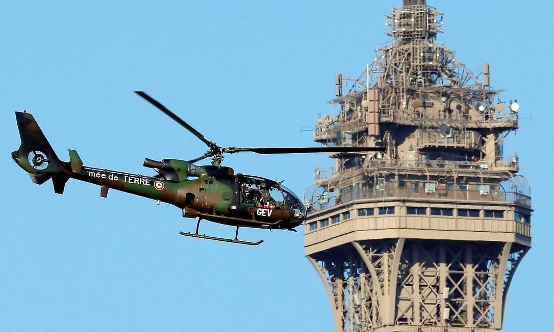 Um helicóptero militar francês voa próximo à Torre Eiffel antes do início das celebrações em Paris. GONZALO FUENTES / REUTERS