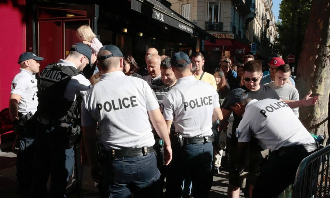 Polícia francesa revista visitantes na entrada de área para assistir a parada militar do Dia da Bastilha. Segurança foi reforçada devido a ameaças terroristas e a presença de Donald Trump. GEOFFROY VAN DER HASSELT / AFP