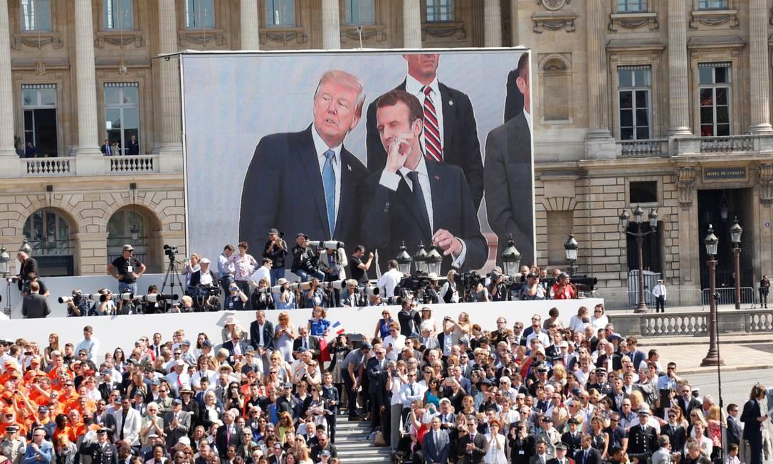 Os presidentes Trump e Macron aparecem em telão gigante. A parada em Paris este ano celebra também o centenário da entrada dos americanos na Primeira Guerra Mundial. KEVIN LAMARQUE / REUTERS