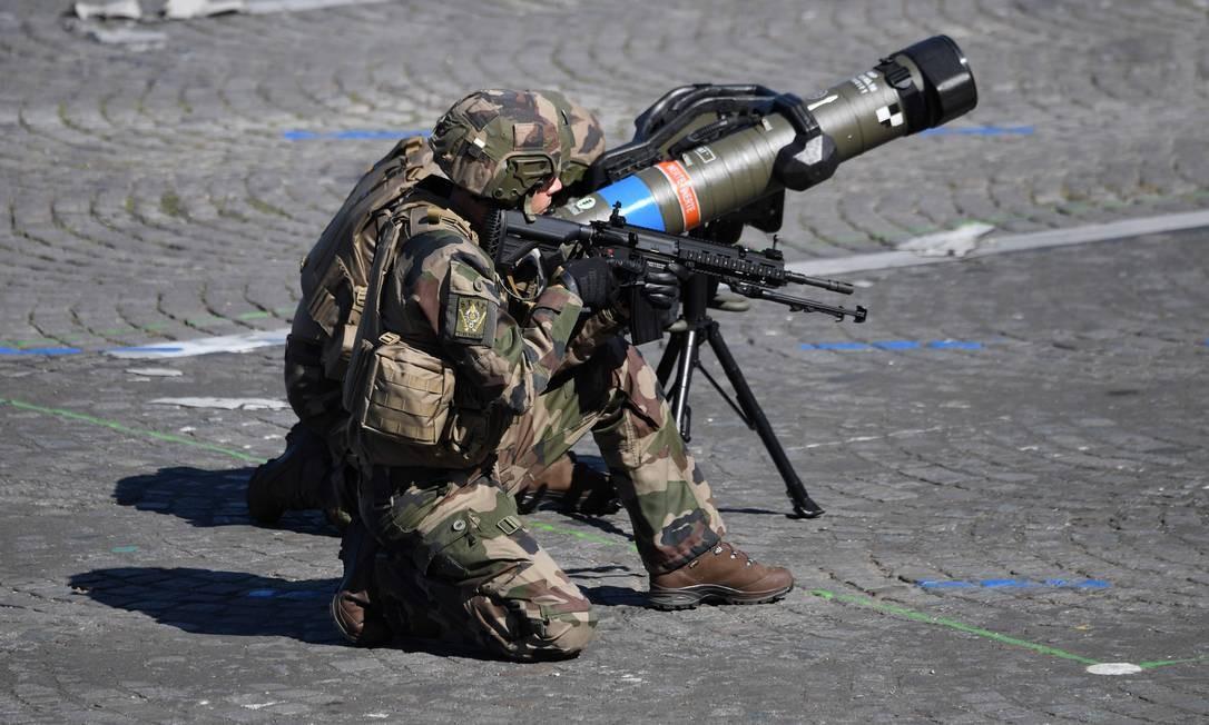 Membro do Exército francês faz exibição com lançador de mísseis anti-tanque durante a anual parada militar. ALAIN JOCARD / AFP