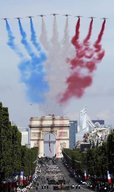 """Pintando o céu com as cores da bandeira da França, a """"Patrouille de France"""", esquadrilha da fumaça francesa, voa sobre a Avenida Champs Elysée, com o Arco do Triunfo ao fundo, em Paris. Markus Schreiber / AP"""