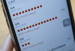 Foto tirada nesta sexta-feira mostra uma mulher tentando publicar um emoji de vela nas redes sociais Foto: STR / AFP