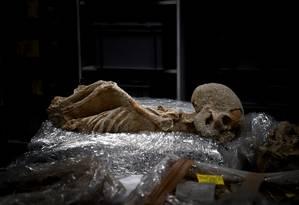 Um dos esqueletos tem as mãos amarradas atrás das costas Foto: ARIS MESSINIS / AFP