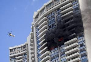 Helicóptero dos bombeiros sobrevoa o edifício em chamas Foto: Marco Garcia / AP
