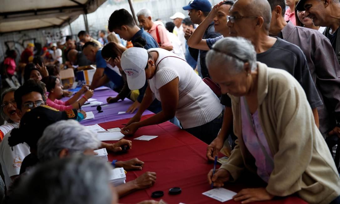 Eleitores dão seu voto no plebiuscto contra o governo de Maduro, convocado pela oposição Foto: CARLOS GARCIA RAWLINS / REUTERS