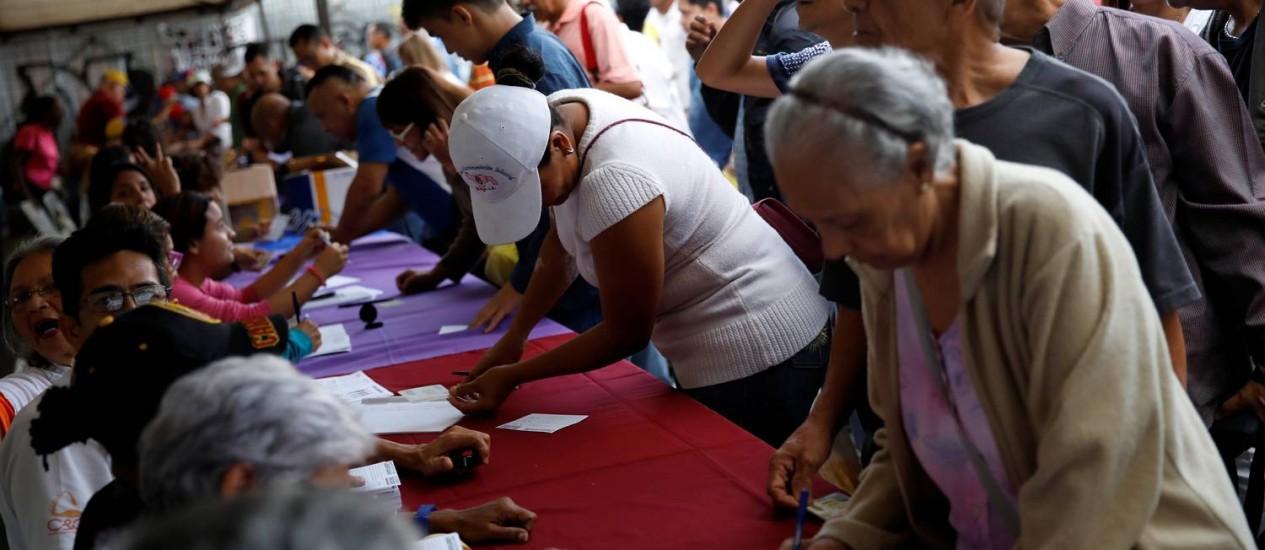 Eleitores dão seu voto no plebiscito contra o governo de Maduro, convocado pela oposição Foto: CARLOS GARCIA RAWLINS / REUTERS