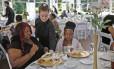 Katelin Decraene, no centro, serve salada a Trishell Crawford e a filha Jacqueline Crawford, de Dayspring, na recepção oferecida no Ritz Charles, no sábado, por Sarah Cummins, que teve seu casamento cancelado e decidiu doar o jantar a desabrigados da região, em Indianapolis, Indiana (EUA)