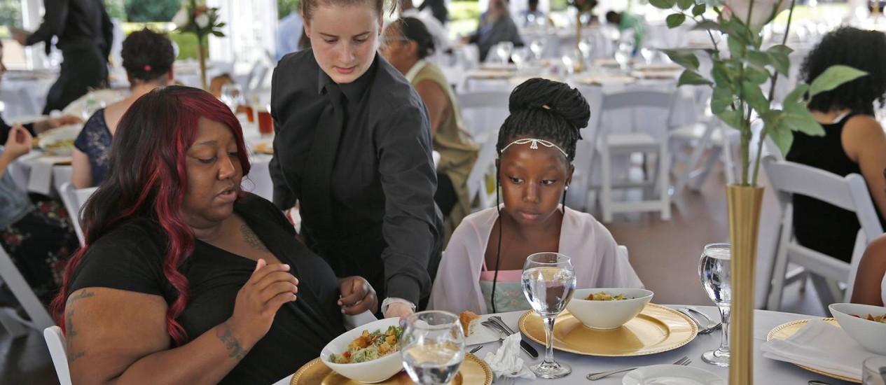 Katelin Decraene, no centro, serve salada a Trishell Crawford e a filha Jacqueline Crawford, de Dayspring, na recepção oferecida no Ritz Charles, no sábado, por Sarah Cummins, que teve seu casamento cancelado e decidiu doar o jantar a desabrigados da região, em Indianapolis, Indiana (EUA) Foto: Kelly Wilkinson / AP