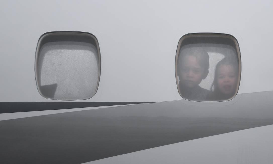 George e Charlotte olham da janela do avião durante o desembarque em Varsóvia, na Polônia BARTLOMIEJ ZBOROWSKI / AFP