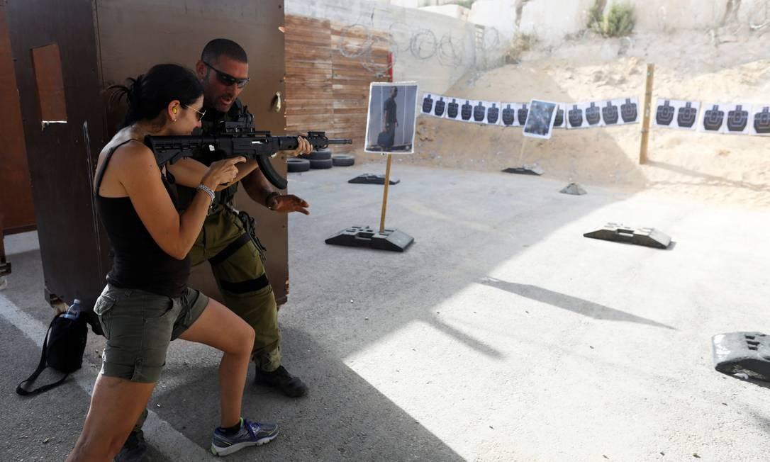 Instrutor israelense ensina a uma turista como empunhar uma arma em um stand de tiros Foto: NIR ELIAS / REUTERS