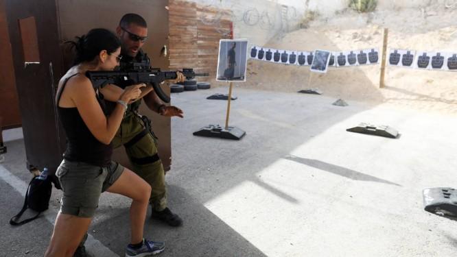 Instrutor israelense ensina a uma turista como empunhar uma arma no Caliber 3, centro de treinamento antiterrorismo na Cisjordânia Foto: NIR ELIAS / REUTERS