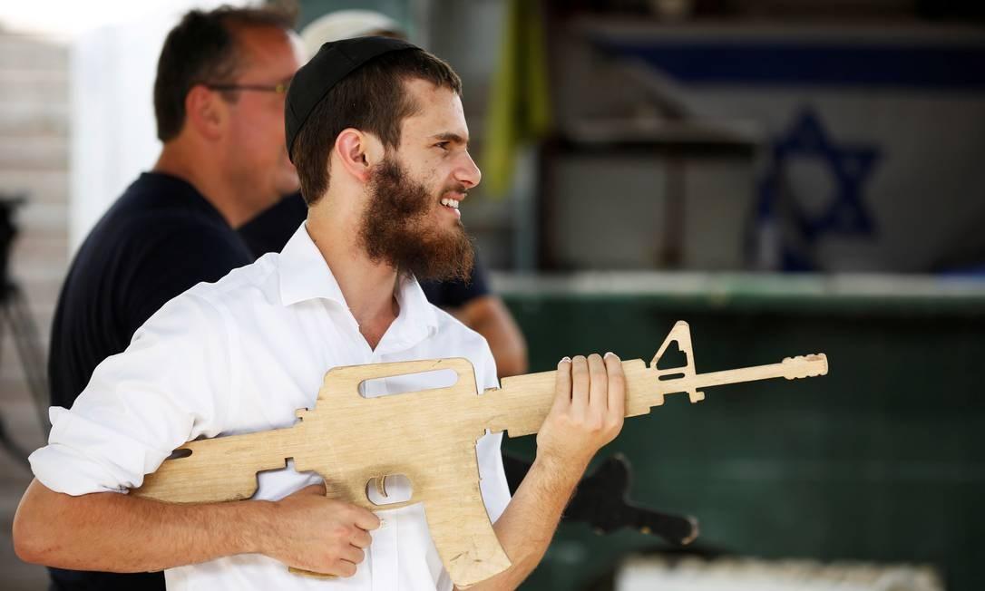 Turista empunha um molde de madeira imitando um fuzil no Caliber 3. O centro de treinamento militar na Cisjordânia oferece a turistas experiências de combate ao terrorismo Foto: NIR ELIAS / REUTERS