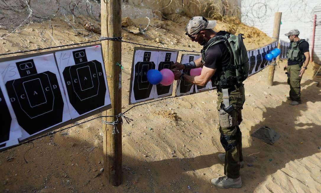 Instrutores do Caliber 3 preparam o stand de tiros para os visitantes Foto: NIR ELIAS / REUTERS