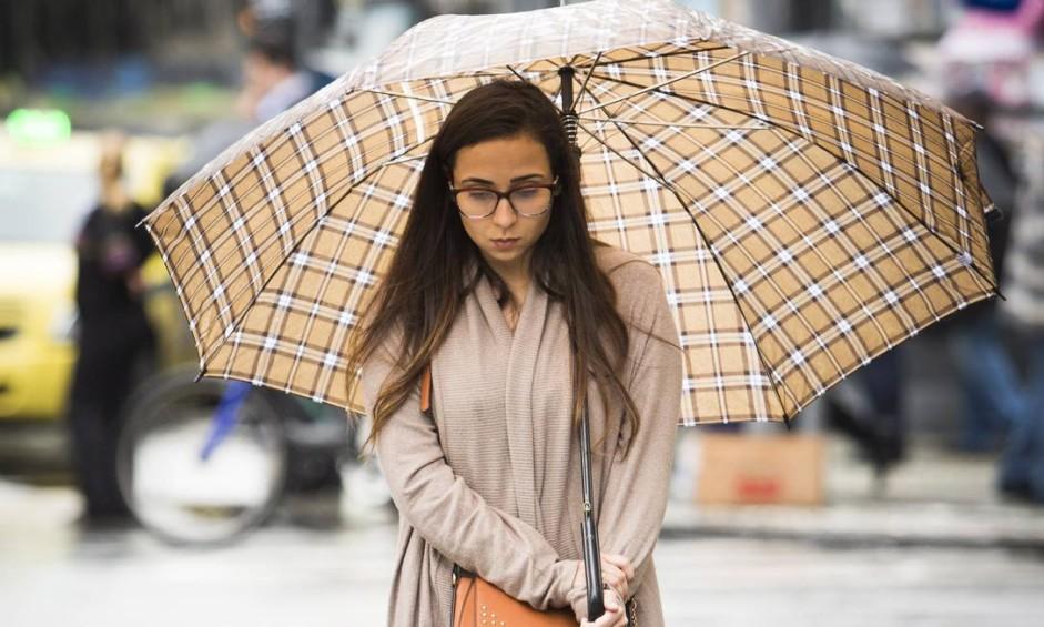 O frio pegou o carioca de jeito nesta quarta-feira. Sob chuva, mulher caminha com blusa longa e calça pelas ruas do Centro do Rio Foto: Monica Imbuzeiro / Agência O Globo